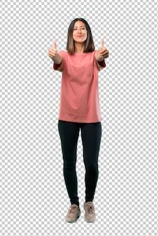 Jong meisje met roze overhemd die duimen op gebaar met beide handen en het glimlachen geven