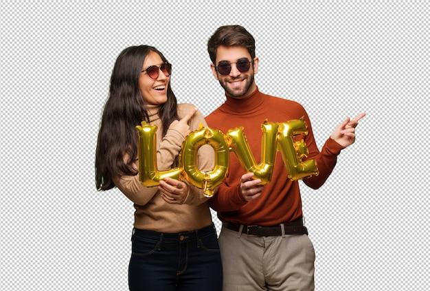 Jong paar in de dag van valentijnskaarten glimlachend en wijst naar de kant
