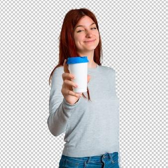 Jong roodharigemeisje die hete koffie in meeneemdocument kop houden