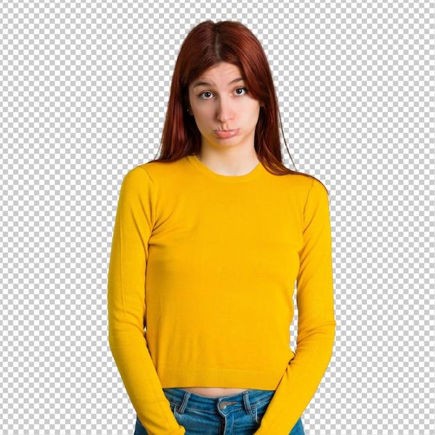 Jong roodharigemeisje met gele sweater met droevige en gedeprimeerde uitdrukking. ernstig gebaar