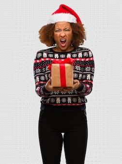 Jong zwarte die een gift in kerstmisdag houden die zeer boos en agressief gillen