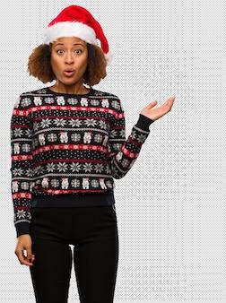 Jong zwarte in een trendy kerstmissweater met druk die iets op palmhand houden