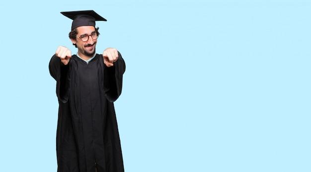 Jonge afgestudeerde man lacht vrolijk en wijst naar voren, u te kiezen.