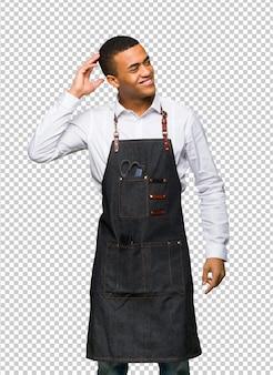 Jonge afro amerikaanse kappersmens die een idee denkt terwijl het krassen van hoofd