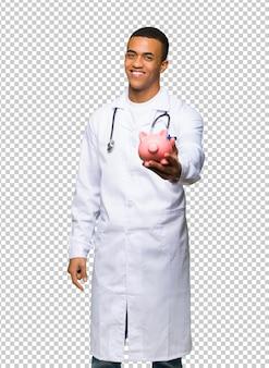 Jonge afro amerikaanse mens arts die een piggybank houdt