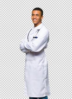 Jonge afro amerikaanse mens arts die over de schouder met een glimlach kijkt