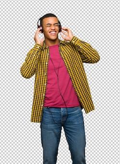 Jonge afro amerikaanse mens die aan muziek met hoofdtelefoons luistert