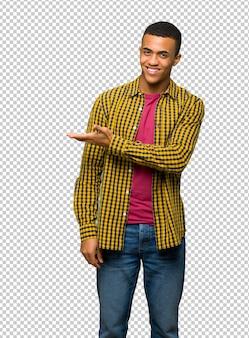 Jonge afro amerikaanse mens die een idee voorstelt terwijl het kijken naar het glimlachen