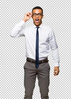 Jonge afro-amerikaanse zakenman met een bril en verrast
