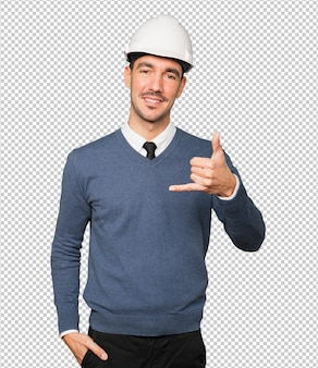 Jonge architect die een gebaar maakt van bellen met zijn hand