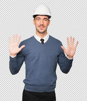 Jonge architect die een gebaar maakt van nummer tien