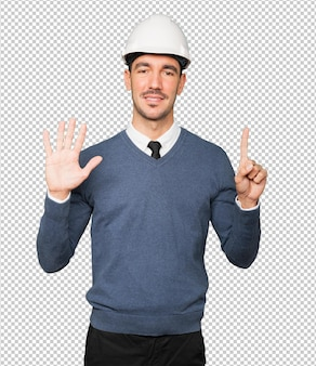 Jonge architect die een gebaar maakt van nummer zes