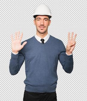 Jonge architect die een gebaar van nummer acht maakt