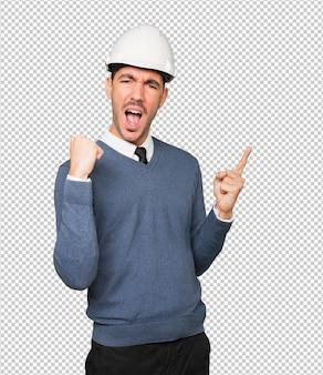 Jonge architect die een gebaar van viering maakt en met zijn vinger wijst
