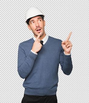 Jonge architect die een twijfelgebaar maakt en met zijn vinger wijst