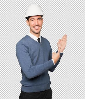 Jonge architect die met zijn hand een verwelkomend gebaar maakt