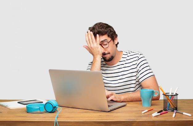 Jonge, bebaarde grafische ontwerper met een laptop die ongemotiveerd en verveeld kijkt