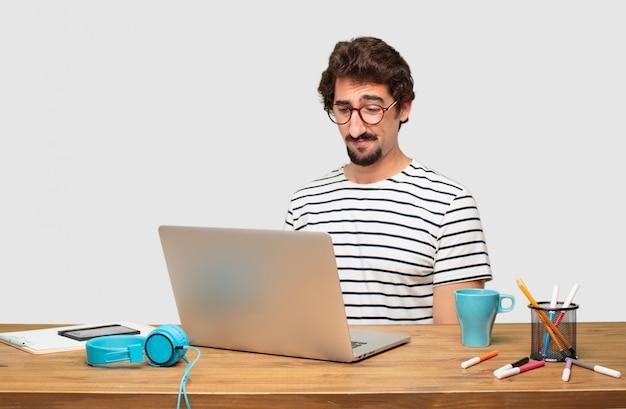 Jonge, bebaarde grafische ontwerper met een laptop met een droevige blik van teleurstelling en nederlaag