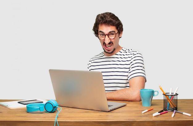 Jonge, bebaarde grafische ontwerper met een laptop op zoek boos, ongelukkig en gefrustreerd