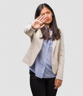 Jonge bedrijf indiase vrouw serieus en vastberaden, hand in de voorkant, stop gebaar, ontkenning concept