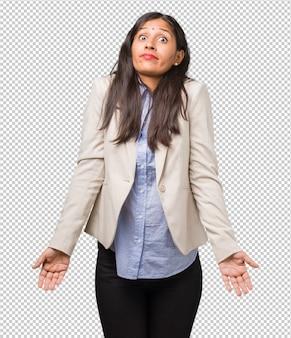 Jonge bedrijfs indische vrouw die en schouders twijfelt ophaalt
