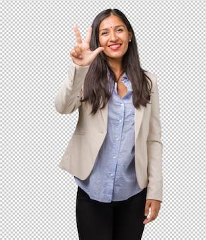 Jonge bedrijfs indische vrouw die nummer drie, symbool van het tellen, concept wiskunde tonen, zeker en vrolijk
