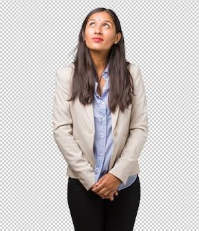 Jonge bedrijfs indische vrouw omhoog kijkend, denkend aan iets pret en hebbend een idee