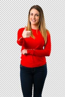 Jonge blonde vrouw die duimen op gebaar en het glimlachen geeft