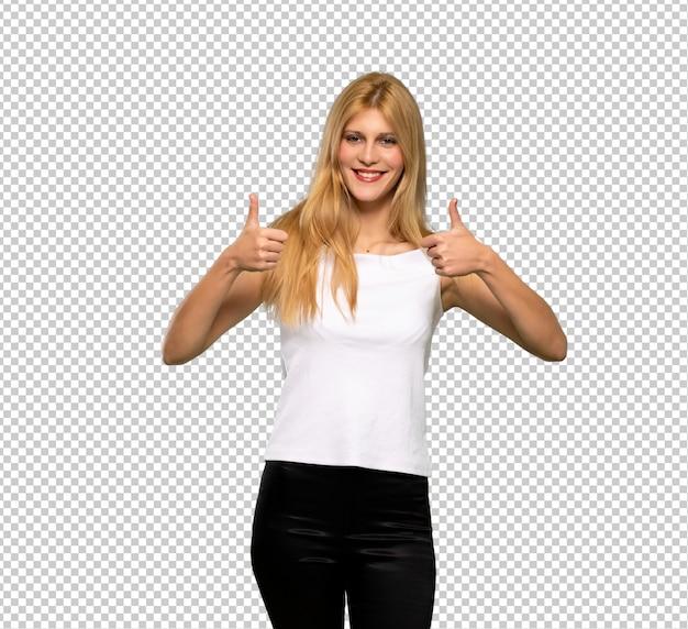 Jonge blonde vrouw die duimen op gebaar geeft omdat iets goed is gebeurd