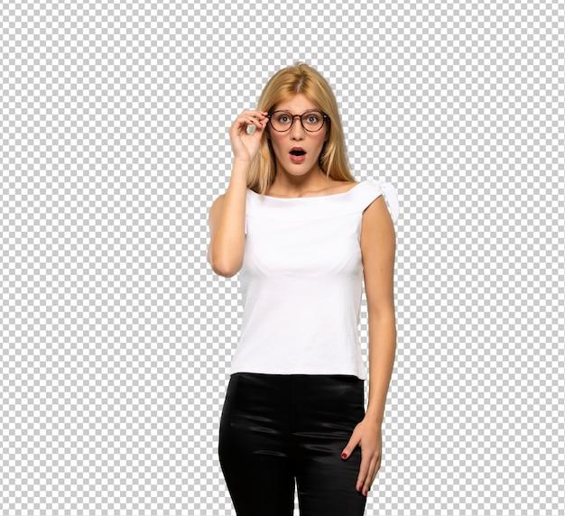 Jonge blonde vrouw met een bril en verrast