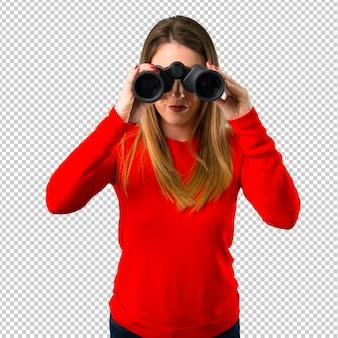 Jonge blonde vrouw met een verrekijker