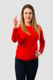 Jonge blondevrouw die een ok teken met vingers tonen