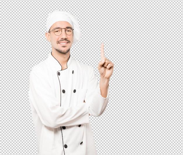 Jonge chef-kok die een gebaar nummer één maakt