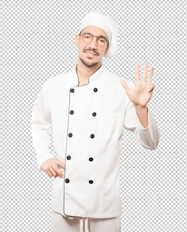 Jonge chef-kok die een gebaar nummer vier maakt