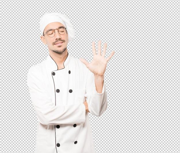 Jonge chef-kok die een gebaar nummer vijf maakt