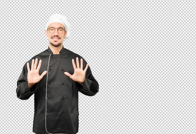Jonge chef-kok die een gebaar van nummer tien maakt