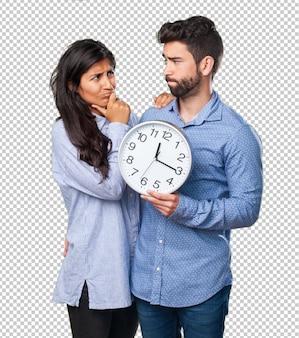 Jonge couplg die een klok houdt