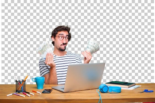 Jonge gekke grafische ontwerper op een bureau met laptop en betaal, het kopen of geldconcept