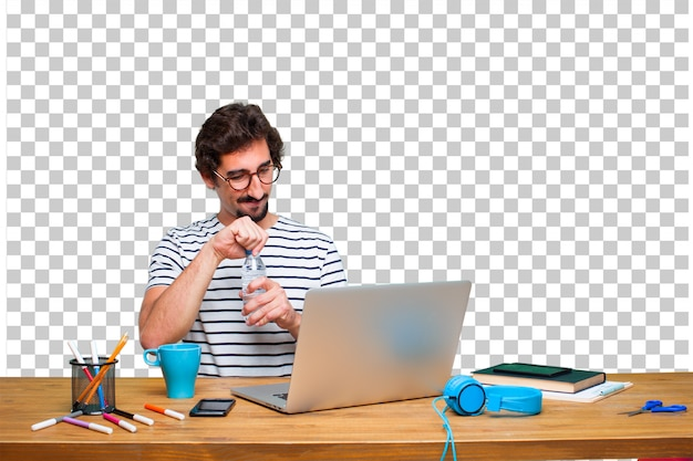 Jonge gekke grafische ontwerper op een bureau met laptop en een waterfles