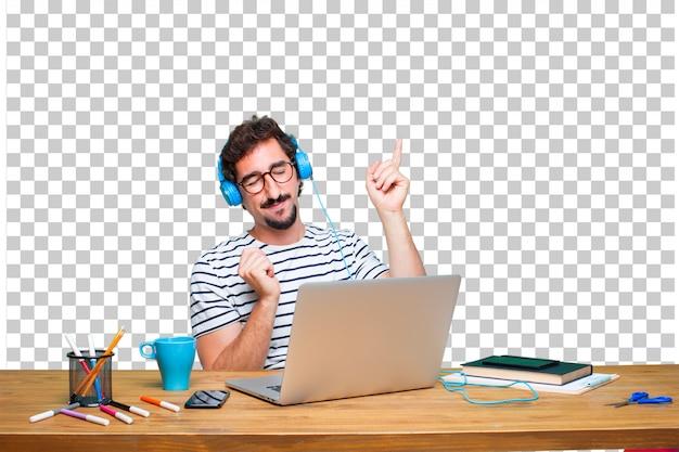 Jonge gekke grafische ontwerper op een bureau met laptop en het luisteren muziek met hoofdtelefoons