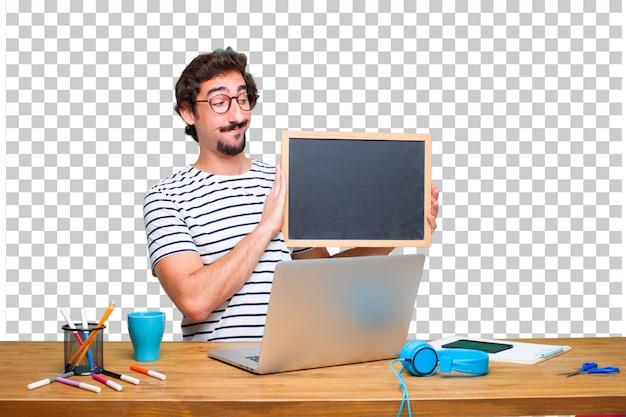 Jonge gekke grafische ontwerper op een bureau met laptop en met een aanplakbiljet