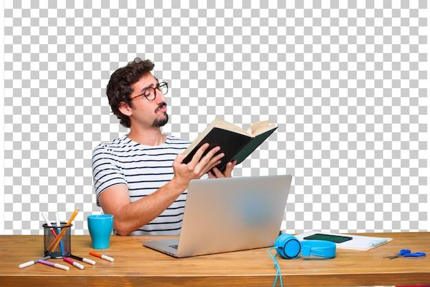 Jonge gekke grafische ontwerper op een bureau met laptop en met een boek