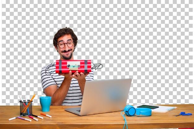 Jonge gekke grafische ontwerper op een bureau met laptop en met een dynamietbom