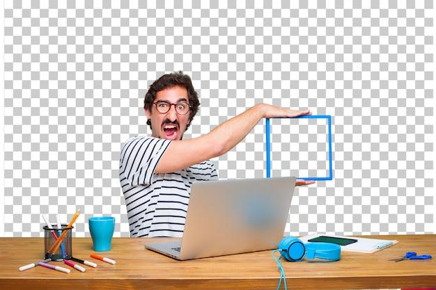 Jonge gekke grafische ontwerper op een bureau met laptop en met een frame