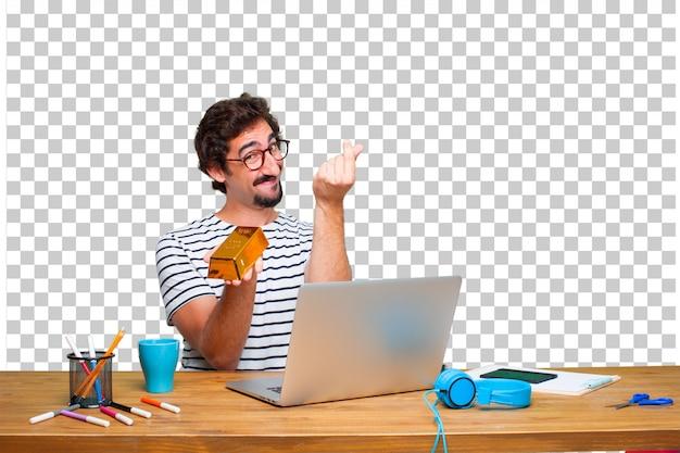 Jonge gekke grafische ontwerper op een bureau met laptop en met een gouden baar