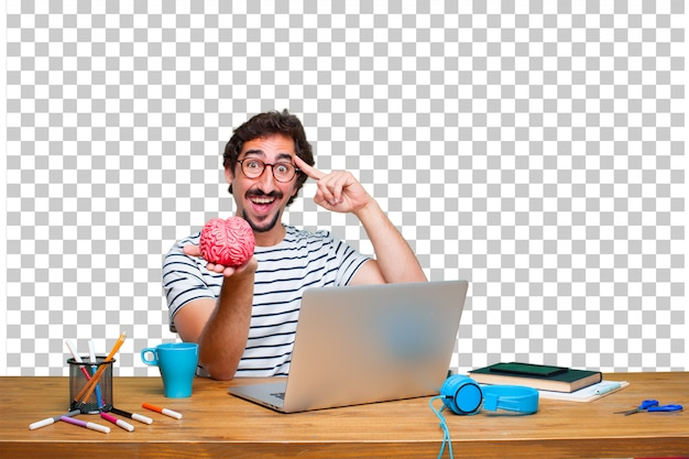 Jonge gekke grafische ontwerper op een bureau met laptop en met een hersenmodel