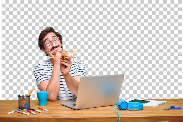 Jonge gekke grafische ontwerper op een bureau met laptop en met een houten vliegtuig
