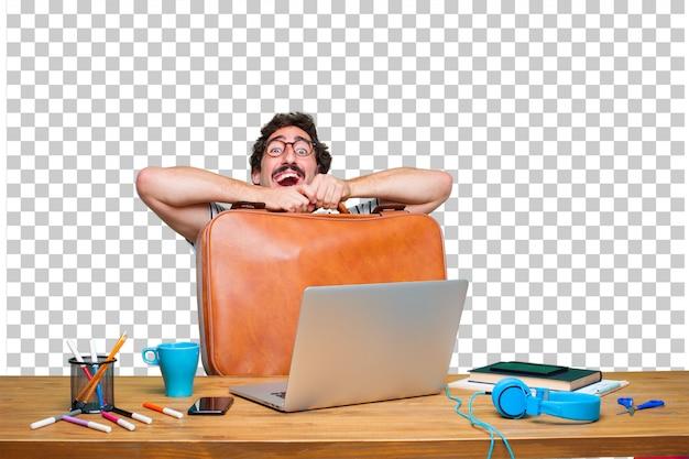 Jonge gekke grafische ontwerper op een bureau met laptop en met een koffer van het leergeval