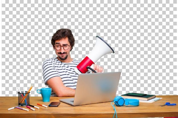 Jonge gekke grafische ontwerper op een bureau met laptop en met een megafoon