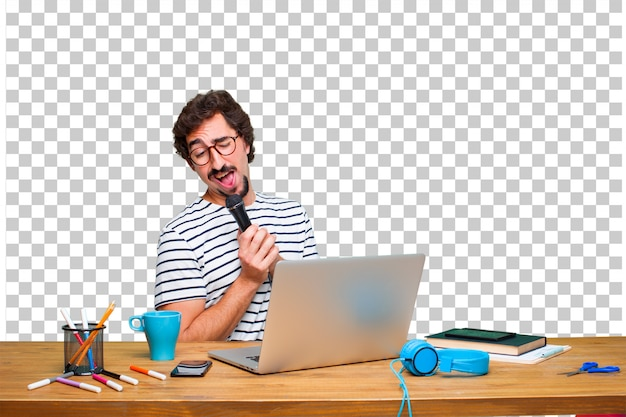 Jonge gekke grafische ontwerper op een bureau met laptop en met een microfoon